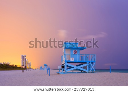 Summer scene in Miami Beach Florida, with a blue lifeguard house in a typical Art Deco architecture, at sunset with ocean and colorful sky in the background - stock photo