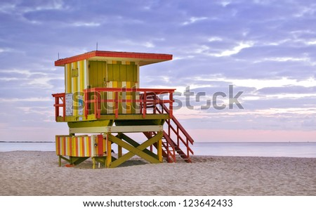 Summer scene in Miami Beach Florida, with a colorful lifeguard house in a typical Art Deco architecture, moments before sunrise with blue sky in the background. Light painting and long exposure. - stock photo