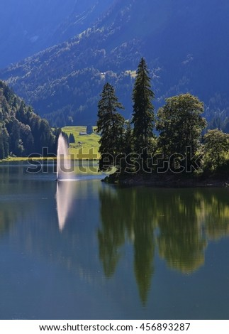 Summer scene in the Swiss Alps. Travel destination lake Obersee. Firs and fountain. - stock photo