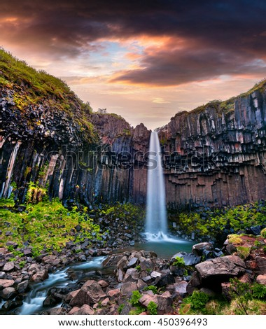 Summer scene of famous Svartifoss (Black Fall) Waterfall. Colorful sunrise in Skaftafell, Vatnajokull National Park, Iceland, Europe.  - stock photo