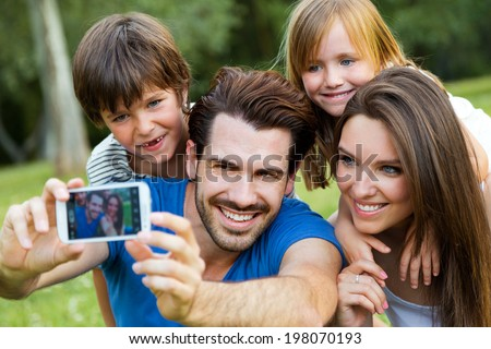 Summer scene of Happy young family taking selfies with her smartphone in the park - stock photo