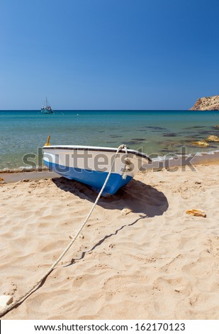 Summer seascape in a Greek island with a small boat on the beach - stock photo