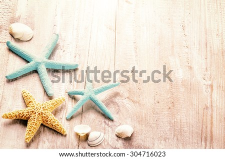 Summer setting with sea shells on old wooden background - stock photo