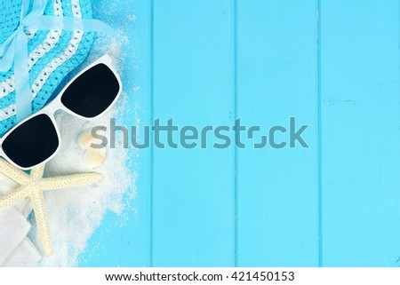 Summer side border of beach items and sea shells on blue wooden background - stock photo