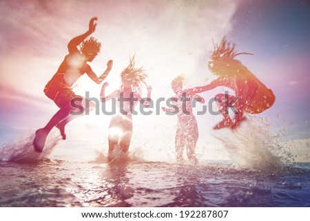 summer silhouettes of happy young people jumping in sea on the beach. vintage retro style with soft focus and sun flare - stock photo