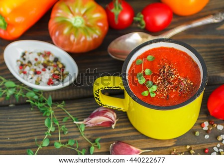 Summer soup. Delicious homemade thick soup of fresh vegetables - tomatoes, bell peppers, garlic with herbs, spices and olive oil.  Selective focus - stock photo
