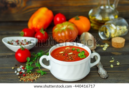Summer soup. Delicious homemade thick soup of fresh vegetables - tomatoes, bell peppers, garlic with herbs, spices, sunflower seeds and olive oil - stock photo