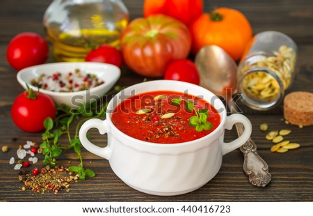 Summer soup. Gourmet soup of fresh tomatoes with herbs, spices, sunflower seeds and olive oil - stock photo