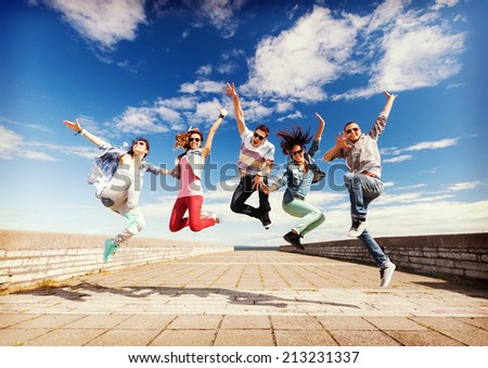 summer, sport, dancing and teenage lifestyle concept - group of teenagers jumping - stock photo