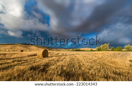 Summer storms rage over recently harvested wheat field in Tuscany, Italy - stock photo