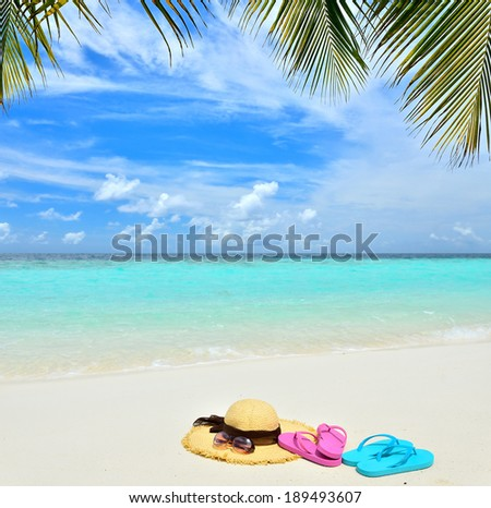 Summer straw hat with sun glasses and flip flops on a tropical sandy beach -- vacation concept  - stock photo