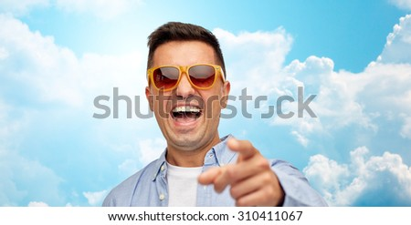 summer, style, emotions and people concept - face of laughing middle aged latin man in shirt and sunglasses over blue sky and clouds background - stock photo