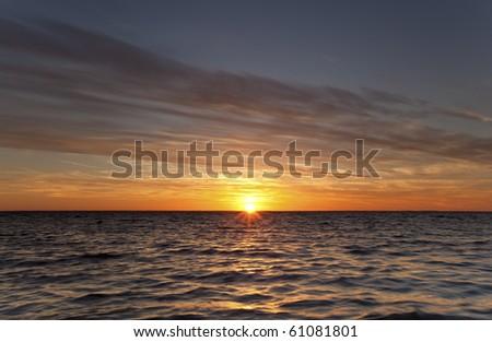 Summer sun goes down over the ocean, Swedish coastline - stock photo