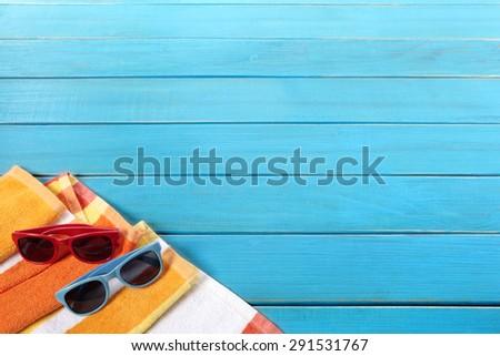 Summer sunbathing beach background, sunglasses, towel, copy space - stock photo