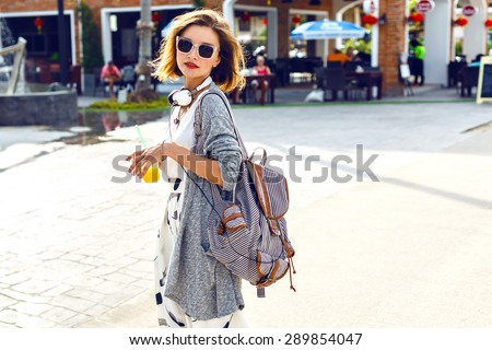 Summer sunny lifestyle fashion portrait of young stylish hipster woman walking on the street, wearing cute trendy outfit, drinking tasty smoothie, smiling enjoy her weekends, travel with backpack/ - stock photo