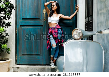 Summer sunny lifestyle portrait of young stylish hipster woman walking on the street,wearing cute trendy outfit,drive scooter,vespa,smiling and laughing,travel girl Chinese Asian / Caucasian woman - stock photo
