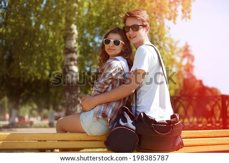 Summer sunny portrait happy urban young couple in sunglasses enjoying summer time in city park, lifestyle - stock photo