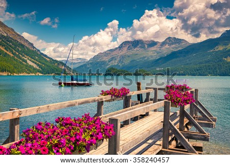 Summer sunny scene on the Silsersee lake with yacht and blooming flowers. Swiss Alps. Segl, Switzerland, Europe. Retro style filtered. - stock photo