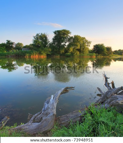 Summer sunrise on the river bank - stock photo