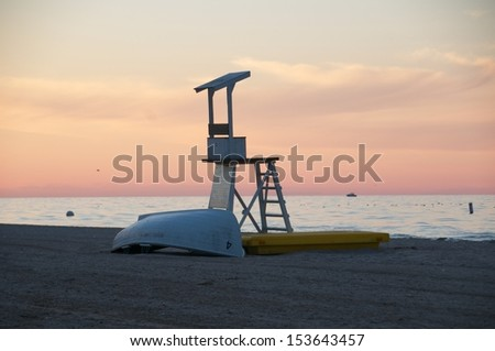 Summer sunset at the beach with the empty life guard tower and the turned over rowboat laying on the sand - stock photo