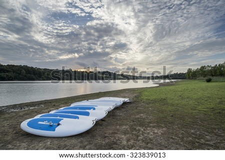 Summer sunset over lake in landscape with leisure boats on shore - stock photo