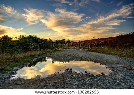 Summer sunset with clouds reflecting in puddle. - stock photo