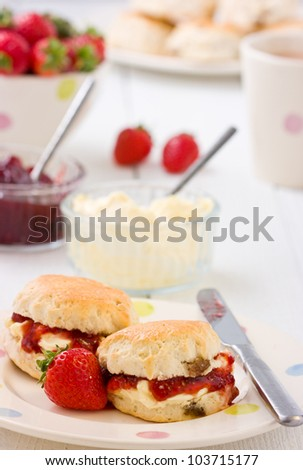 Summer time on a plate with scones, strawberry jam, clotted cream strawberries, and tea on a white rustic table. - stock photo