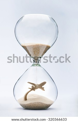 Summer travel. Hourglass falling sand taking the shape of a plane taking off - stock photo