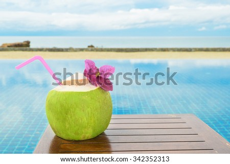 Summer, Travel, Vacation and Holiday concept - Tropical fresh coconut cocktail with pool and beach in ocean, Phuket ,Thailand - stock photo