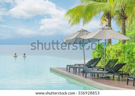 Summer, Travel, Vacation and Holiday concept - Umbrella and chair with pool in hotel resort - stock photo