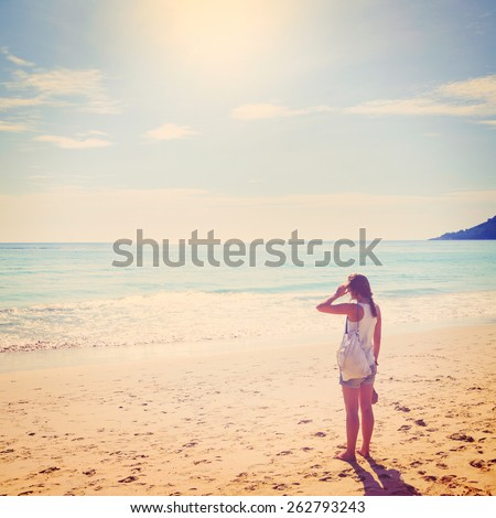 summer travel. young woman is standing on beach - stock photo