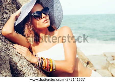 Summer trendy fashion woman posing on the rocks alone on the ocean seashore. Outdoors lifestyle portrait - stock photo