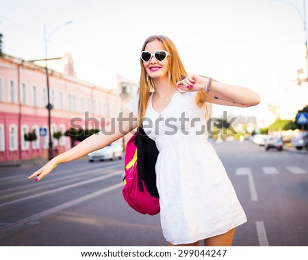Summer trendy portrait of beautiful young hipster traveler girl.travel, vacation,people, tourism concept - smiling young woman waving hand and catching taxi at airport terminal or railway station  - stock photo