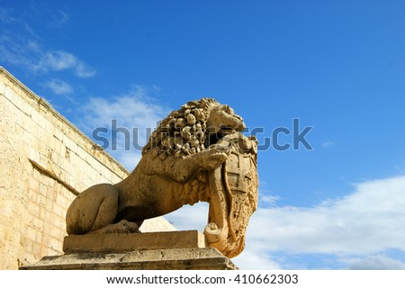 Summer vacation and trip to Malta. The figure of a lion on a hill at the gates of the ancient capital Mdina. - stock photo