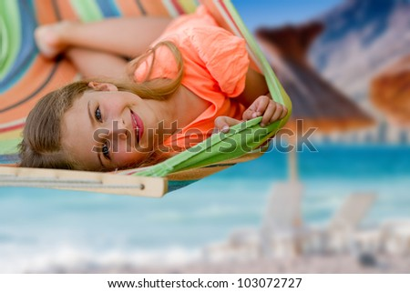 Summer vacation, beach resort - lovely girl in colorful hammock - stock photo