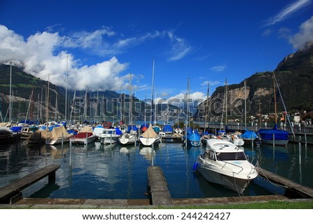 Summer Vacation - Boats parking on Lake Lucerne under blue sky and majestic mountains  - stock photo