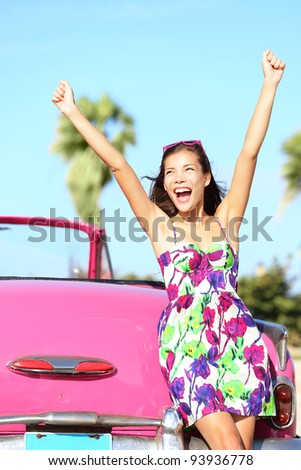 Summer vacation car road trip freedom concept. Happy woman cheering joyful during holiday travel in pink vintage car. Beautiful young mixed race Caucasian / Chinese Asian female model in Havana, Cuba - stock photo