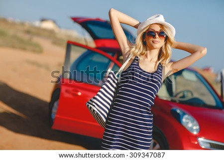Summer vacation. Car trip. Travelling. Car travel. By the sea. Beautiful blonde woman standing with red small car on the background. Sea style. Summer vacation car road trip freedom concept.  - stock photo