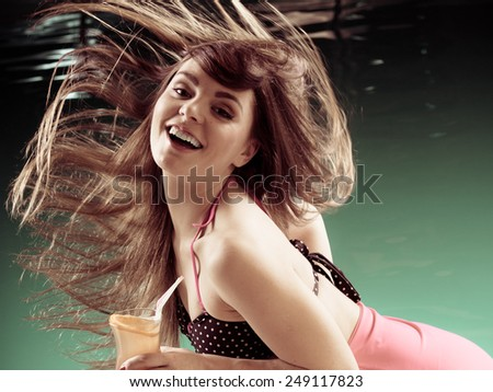 Summer vacation, carefree and happiness concept. Happy young woman in swimsuit holding coctail drink hair in motion on pool water background - stock photo