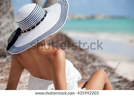 Summer vacation carefree joyful woman sitting on tropical beach. Caribbean vacation. - stock photo