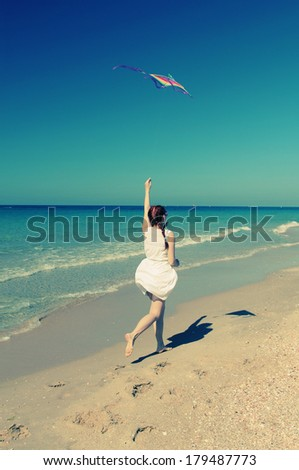 Summer vacation concept: beautiful model holding kite and posing at the seaside - stock photo
