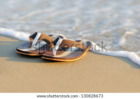 Summer vacation concept. Flip flops on a sandy ocean beach - stock photo