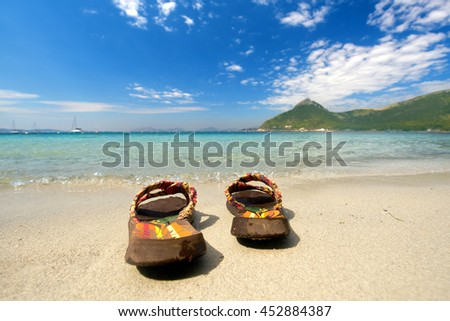Summer vacation concept--Flip flops on a sandy ocean beach                         - stock photo