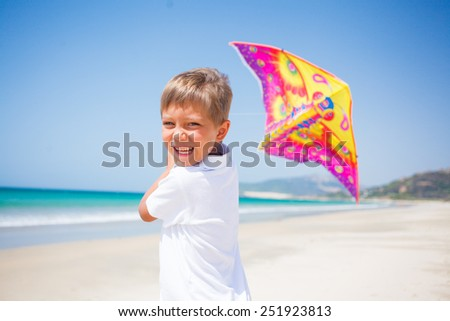 Summer vacation - Cute boy flying kite beach outdoor. - stock photo