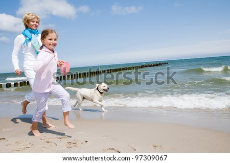 Summer vacation - family with dog playing on the beach - stock photo