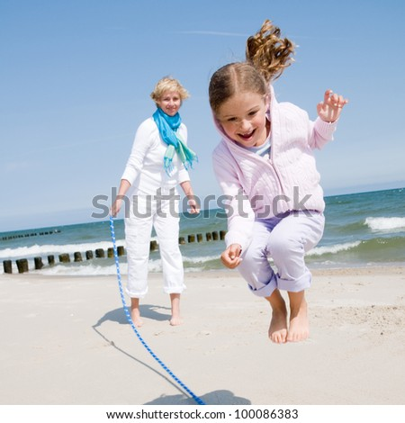Summer vacation - girl playing with skipping rope on the beach - stock photo
