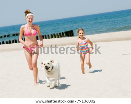 Summer vacation - girls with dog playing on the beach - stock photo
