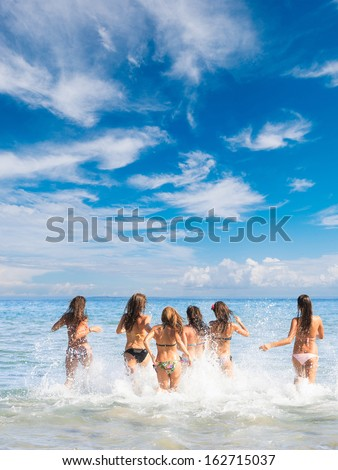 Summer vacation group of six girls playing in the sea - stock photo