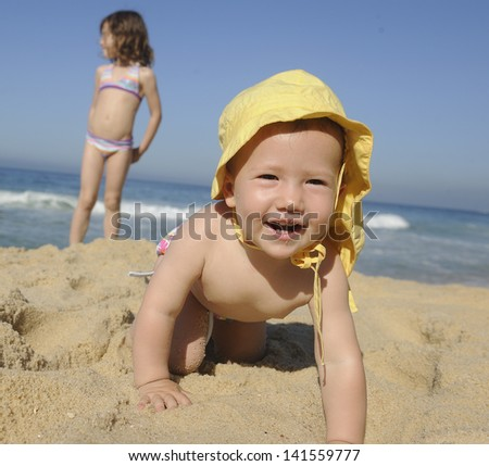 Summer vacation: Happy baby on the beach - stock photo
