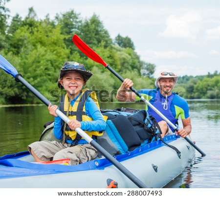 Summer vacation - Happy little boy with his father kayaking on river. - stock photo